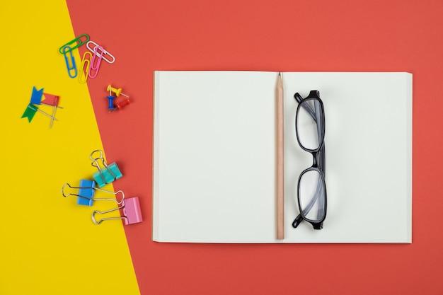 Vista superior del cuaderno abierto en blanco con lápiz y artículos de papelería y anteojos
