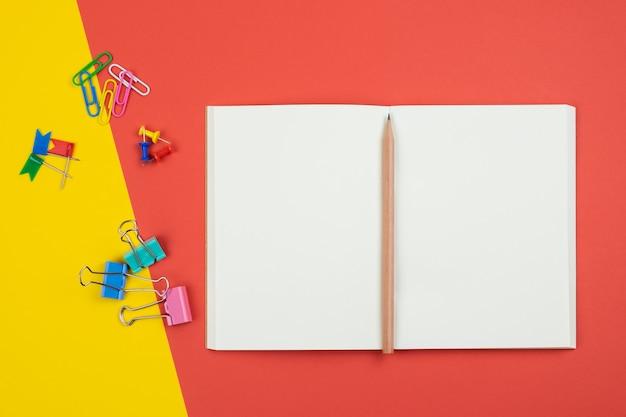 Vista superior del cuaderno abierto en blanco con lápiz y artículos de papelería