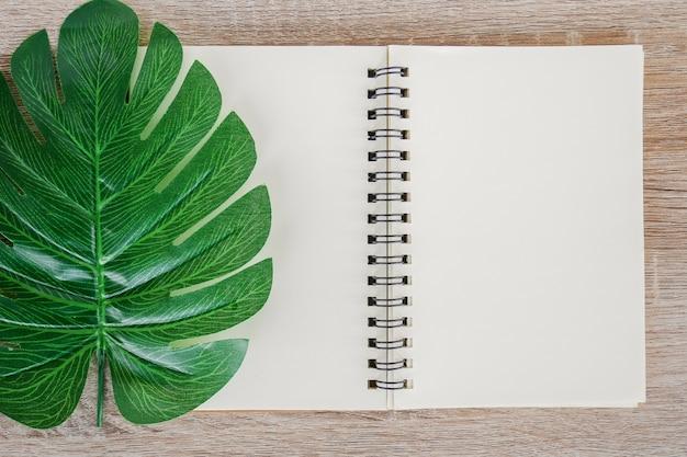 Vista superior del cuaderno abierto en blanco sobre fondo de escritorio de madera con hojas de monstera tropical verde.