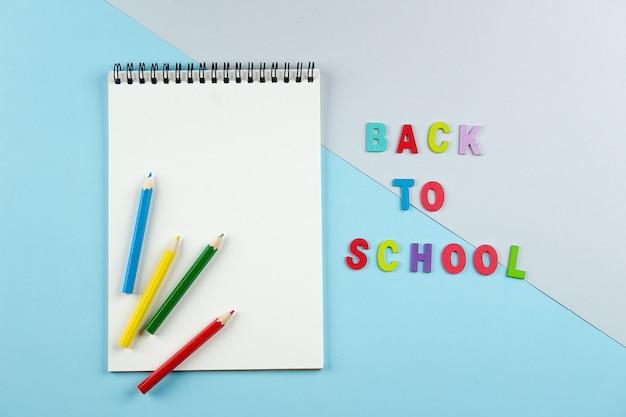 Vista superior del cuaderno abierto con lápices de colores e inscripción de regreso a la escuela