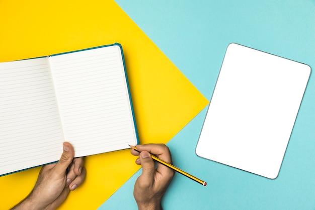 Vista superior cuaderno abierto y tableta maqueta