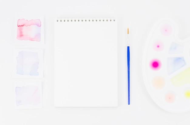 Vista superior cuaderno con acuarela y pincel