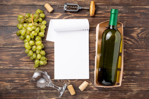 Vista superior del cuaderno al lado de la botella de vino