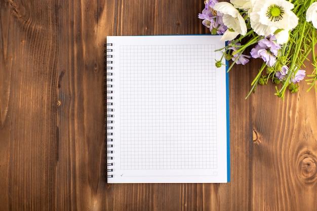 Vista superior del cuaderno azul abierto con flores en el escritorio marrón
