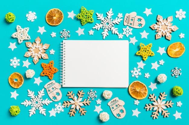 Vista superior del cuaderno en azul con juguetes y decoraciones de año nuevo.