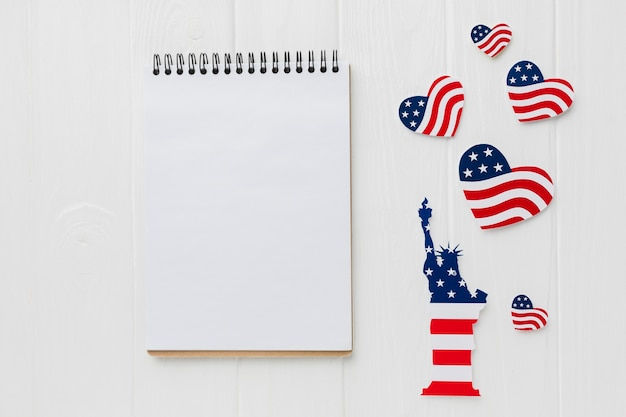 Vista superior del cuaderno con banderas americanas para el día de la independencia y la estatua de la libertad
