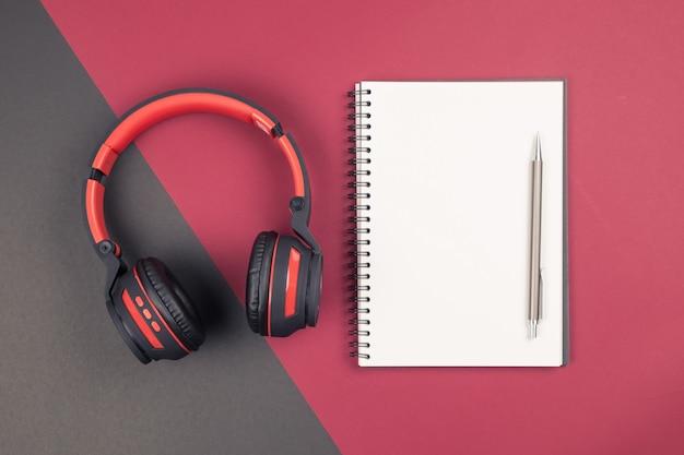 Vista superior del cuaderno en blanco con bolígrafo y auriculares