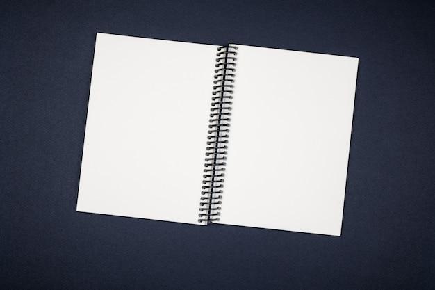 Vista superior del cuaderno en blanco espiral abierto en escritorio colorido