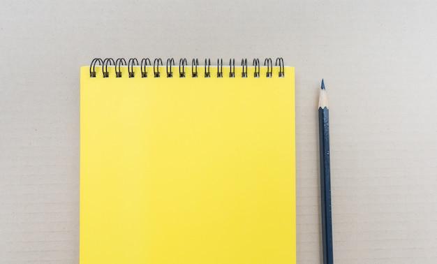 Vista superior del cuaderno en blanco espiral abierto con lápiz sobre fondo marrón.
