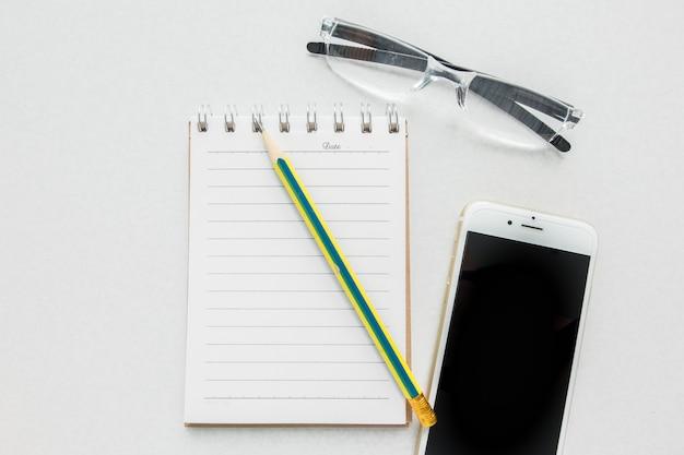 Vista superior del cuaderno en blanco con lápiz, gafas de lectura y teléfono móvil inteligente en mesa blanca.