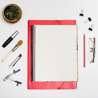 Vista superior de cuaderno en blanco con productos cosméticos; clips de papel; lápiz; anteojos sobre escritorio blanco