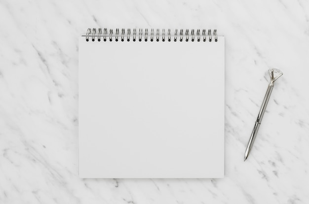 Vista superior del cuaderno blanco sobre escritorio de mármol