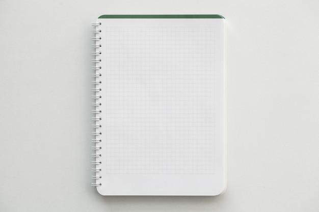 Vista superior del cuaderno blanco sobre mesa blanca