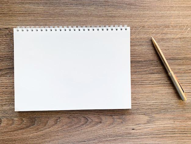 Vista superior del cuaderno blanco sobre mesa de madera