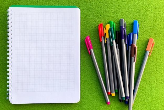 Vista superior del cuaderno blanco sobre mesa verde