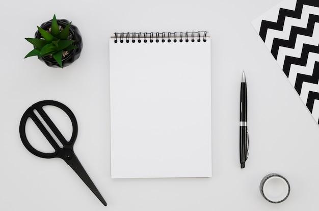 Vista superior del cuaderno en blanco con tijeras y planta