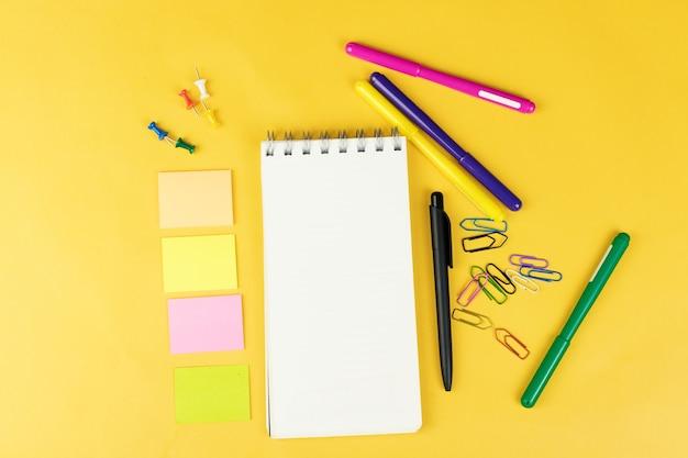 Vista superior del cuaderno en blanco y útiles escolares como marcadores de colores, adhesivos y clipers sobre fondo amarillo, espacio para texto.