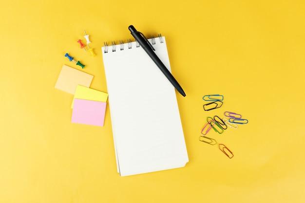 Vista superior del cuaderno en blanco y útiles escolares como marcadores de colores, adhesivos y clipers sobre fondo amarillo.