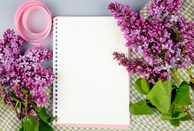 Vista superior de un cuaderno de bocetos con flores de color lila sobre tela a cuadros sobre fondo blanco.