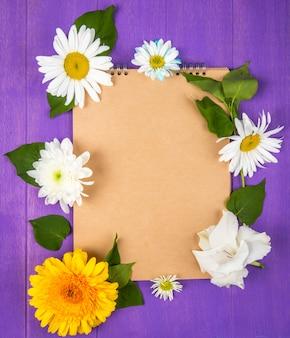 Vista superior de un cuaderno de bocetos con flores de margarita y gerbera sobre fondo de madera púrpura