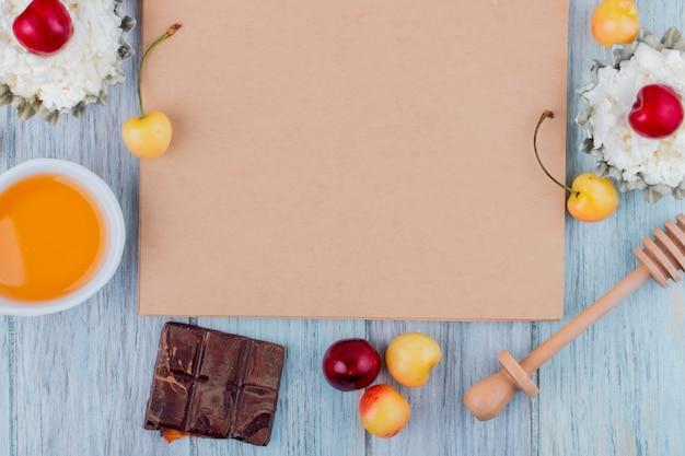 Vista superior del cuaderno de bocetos y queso cottage con miel de chocolate negro y cerezas rojas y amarillas maduras frescas dispuestas en gris