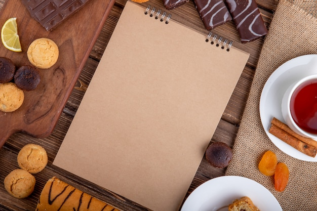 Vista superior del cuaderno de bocetos varias galletas dulces y una taza de té con palitos de canela sobre fondo de madera