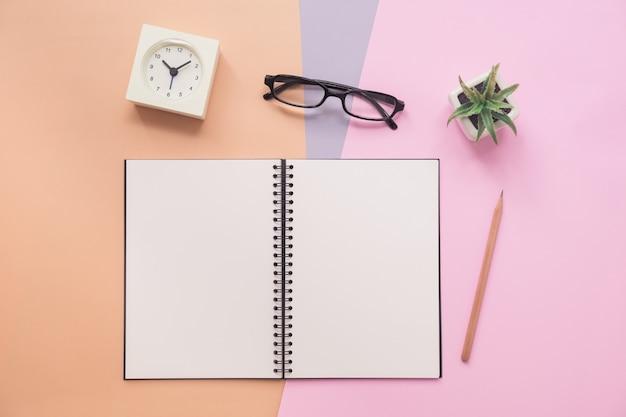 Vista superior del cuaderno con bolígrafo, anteojos, reloj