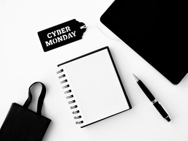 Vista superior del cuaderno con bolsa de compras y etiqueta para cyber monday