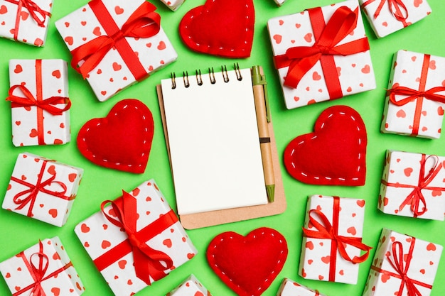 Vista superior del cuaderno, cajas de regalo blancas y corazones textiles rojos sobre fondo colorido. concepto de san valentín