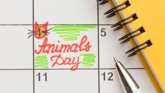 Vista superior del cuaderno y calendario para el día de los animales.