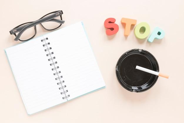 Vista superior cuaderno con cenicero y gafas