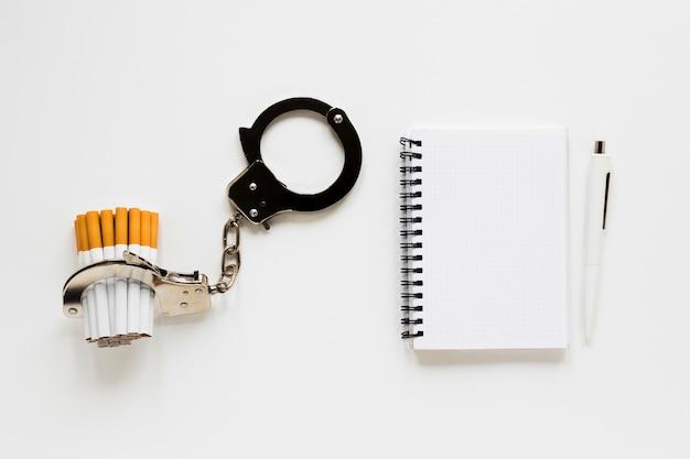 Vista superior cuaderno con cigarros y esposas