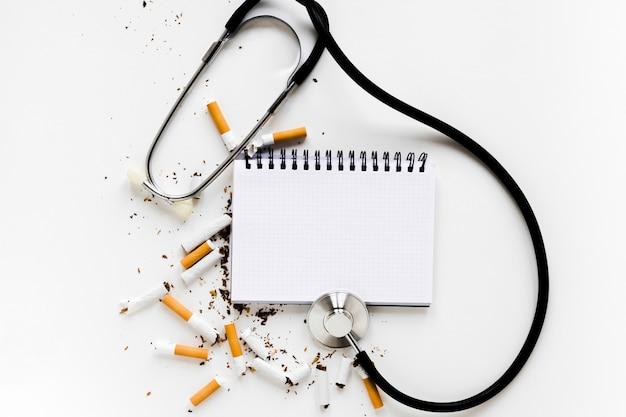 Vista superior cuaderno con cigarros y fonendoscopio