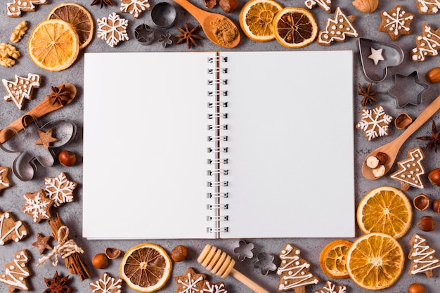 Vista superior del cuaderno con cítricos secos y pan de jengibre