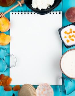 Vista superior de un cuaderno de dibujo y duraznos maduros frescos albaricoques secos yogur de requesón y cortadores de galletas dispuestos en azul