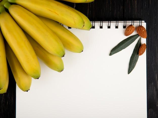 Vista superior de un cuaderno de dibujo y fresco racimo de plátano con almendras en negro
