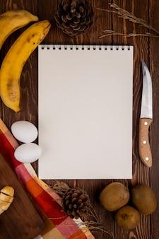 Vista superior de un cuaderno de dibujo con kiwi y plátano y dos huevos con cuchillo de cocina en madera