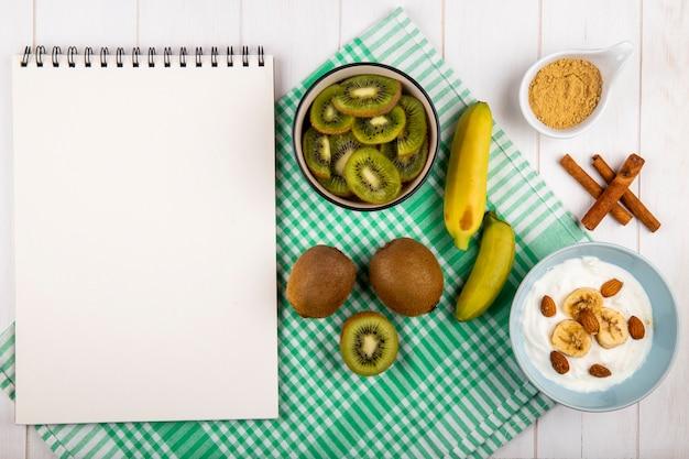 Vista superior de un cuaderno de dibujo, rodajas de kiwi en un tazón, frutas frescas de plátano, yogurt con rodajas de plátano con almendras y palitos de canela en madera blanca
