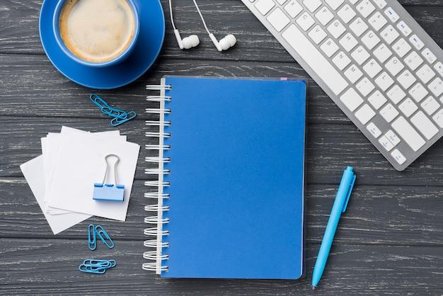 Vista superior del cuaderno en el escritorio de madera con notas adhesivas y taza de café