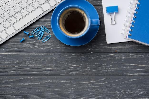 Vista superior del cuaderno en el escritorio de madera con taza de café y teclado