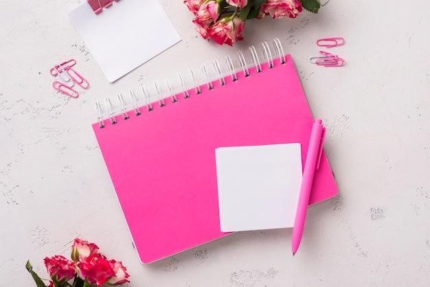 Vista superior del cuaderno en el escritorio con ramo de rosas y bolígrafo