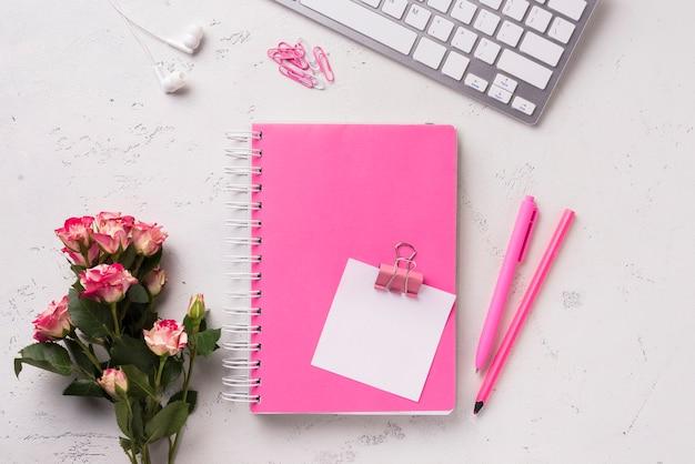 Vista superior del cuaderno en el escritorio con ramo de rosas y bolígrafos