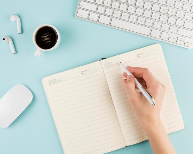 Vista superior del cuaderno en el escritorio con teclado y café