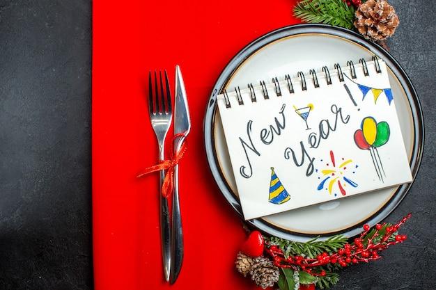 Vista superior del cuaderno con escritura de año nuevo y dibujos en un plato con accesorios de decoración, ramas de abeto y cubiertos en una servilleta roja
