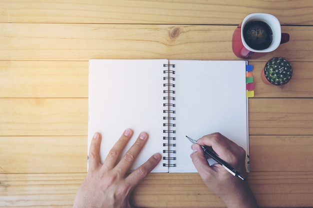 Vista superior del cuaderno de escritura de hombre en mesa de madera con taza de café y olla pequeña de cactus