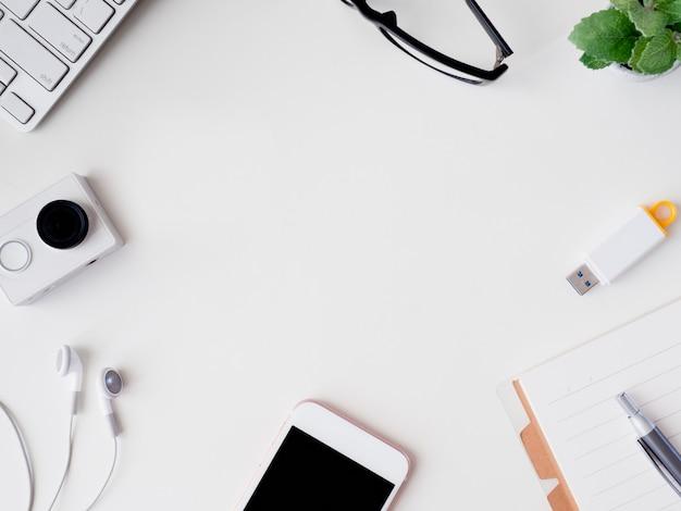 Vista superior del cuaderno de espacio de trabajo del escritorio de oficina, planta de plástico, tableta gráfica sobre fondo blanco con espacio de copia, diseñador gráfico, concepto de diseñador creativo.
