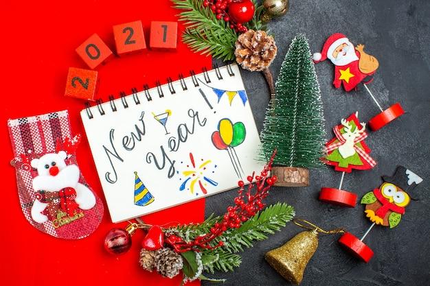 Vista superior del cuaderno espiral con escritura de año nuevo y dibujos, accesorios de decoración, ramas de abeto, números de calcetines navideños en una servilleta roja y árbol de navidad sobre fondo oscuro