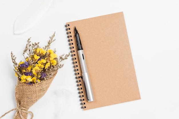 Vista superior del cuaderno espiral de la escuela con pluma y flores estáticas sobre fondo blanco