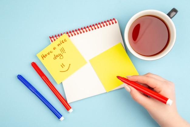 Vista superior del cuaderno espiral taza de té en la mano de la mujer que tenga un buen día escrito en marcadores de papel de nota en azul