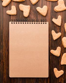 Vista superior del cuaderno y las galletas con forma de corazón del día de san valentín